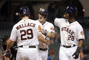 Photo - Houston Astros' Brandon Barnes (2) celebrates with Brett Wallace (29) and L.J. Hoes (28) after all three scored on Barnes' home run to tie the baseball game against the Minnesota Twins during the ninth inning Tuesday, Sept. 3, 2013, in Houston. (AP Photo/David J. Phillip)