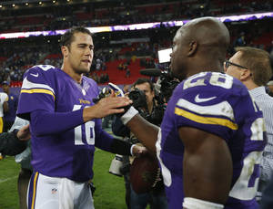 Photo - Minnesota Vikings running back Adrian Peterson (28) shakes hands with quarterback Matt Cassel following their NFL football game against the Pittsburgh Steelers at Wembley Stadium, London, Sunday,Sept. 29, 2013. The Vikings defeated the Steelers 34-27. (AP Photo/Matt Dunham)