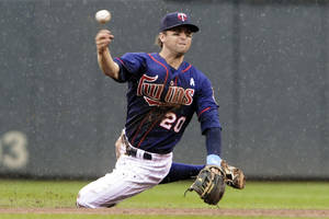 Photo -   Minnesota Twins shortstop Brian Dozier throws out Milwaukee Brewers' Corey Hart after fielding a ground ball in the fifth inning of a baseball game, Sunday, June 17, 2012, in Minneapolis. (AP Photo/Jim Mone)