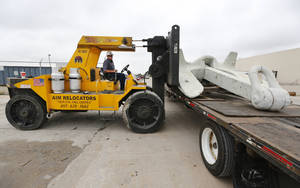 Photo - Curtis Markcum, with AIM Relocators loads an anchor on a flatbed trailer at Government Liquidation's  warehouse in Oklahoma City, Friday September  20, 2013. Photo By Steve Gooch, The Oklahoman <strong>Steve Gooch - The Oklahoman</strong>