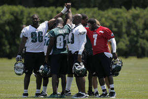 Photo -   From right, Philadelphia Eagles players Michael Vick, DeMeco Ryans, Jason Avant, and Greg Lloyd react with teammates after practice at the team's NFL football training facility, Thursday, May 31, 2012, in Philadelphia. (AP Photo/Matt Rourke)