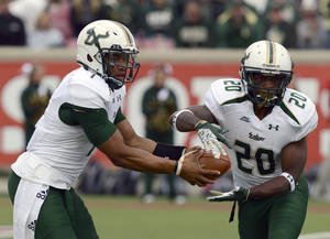 Photo -   South Florida quarterbacl B.J. Daniels, left, hands the ball off to Marcus Shaw during first half action of their NCAA college football game against Louisville Saturday Oct. 20, 2012 in Louisville, Ky. (AP Photo/ Timothy D. Easley)