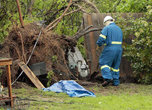 Photo - A gas company employee approaches a leaking meter Friday in Norman after damage from a tornado.