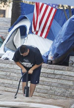 Photo - Occupy OKC protester William Scott Edmonds inflates an air mattress Tuesday.