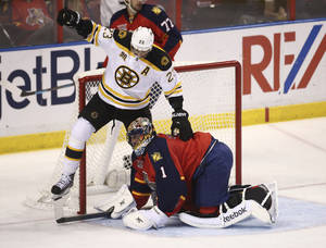 Photo - After Florida Panthers goalie Roberto Luongo (1) blocked the puck, Boston Bruins' Chris Kelly (23) steps over him during the second period of an NHL hockey game in Sunrise, Fla., Sunday, March 9, 2014. (AP Photo/J Pat Carter)