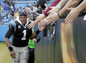 Photo - Carolina Panthers' Cam Newton (1) celebrates with fans after an NFL football game against the New Orleans Saints in Charlotte, N.C., Sunday, Dec. 22, 2013. The Panthers won 17-13. (AP Photo/Bob Leverone)