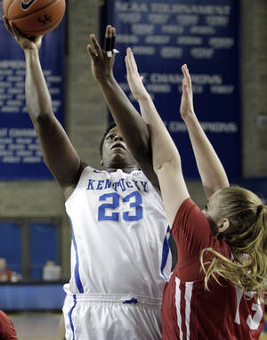 Photo - Kentucky's Samarie Walker (23) shoots under pressure from Alabama's Nikki Hegstetter (13) during the second half of an NCAA college basketball game, Thursday, Jan. 23, 2014, in Lexington, Ky. Alabama won 57-55. (AP Photo/James Crisp)
