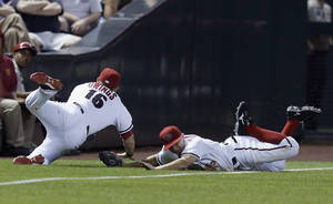Photo - Arizona Diamondbacks' Chris Owings (16) makes a diving catch on a ball hit by Colorado Rockies' Jordan Pacheco as Diamondbacks' Tony Campana, right, also dives for the ball, and the two barely avoid colliding during the eighth inning of a baseball game Tuesday, April 29, 2014, in Phoenix. (AP Photo/Ross D. Franklin)