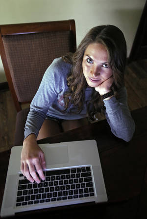 Photo - Mandi Grandjean sits inside her home in Canton, Ohio, Wednesday. Grandjean, a recent graduate of Miami University in Ohio, says she's fine with the government doing secret surveillance of phone call records and Internet exchanges, but  believes it's different when it comes to an employer, or even a coach. AP Photo/Mark Duncan <strong>Mark Duncan - AP</strong>