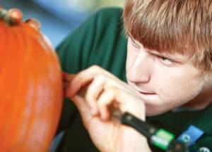 "Photo - Andy Trosper concentrates on his carving as OKC Zoo staff carve pumpkins for ""Haunt the Zoo"", at the Oklahoma City Zoo in Oklahoma City, OK, Tuesday, Oct. 25, 2011. By Paul Hellstern, The Oklahoman ORG XMIT: KOD"