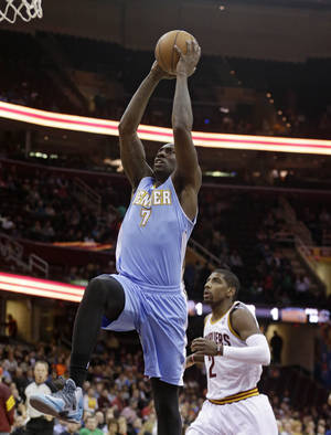 Photo - Denver Nuggets' J.J. Hickson (7) jumps to the basket against Cleveland Cavaliers' Kyrie Irving (2) during the first quarter of an NBA basketball game on Wednesday, Dec. 4, 2013, in Cleveland. (AP Photo/Tony Dejak)