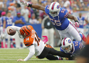 Photo - Cincinnati Bengals quarterback Andy Dalton (14) stretches for more yardage as Buffalo Bills outside linebacker Jerry Hughes (55) dives towards him in the first quarter of the NFL football game on Sunday, Oct. 13, 2013, in Orchard Park, N.Y. (AP Photo/Bill Wippert)