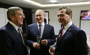 Photo - Russian President Vladimir Putin, center, talks with Prime Minister Dmitry Medvedev, right, and International Olympic Committee President Thomas Bach, left, in the presidential lounge before the 2014 Winter Olympics closing ceremony, Sunday, Feb. 23, 2014, in Sochi, Russia. (AP Photo/David Goldman, Pool)