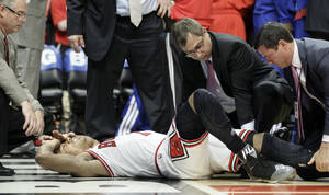 photo -   Chicago Bulls guard Derrick Rose (1) is helped by trainers after an injury during the fourth quarter of Game 1 in the first round of the NBA basketball playoffs against the Philadelphia 76ers in Chicago, Saturday, April 28, 2012. The Bulls won 103-91. (AP Photo/Nam Y. Huh)