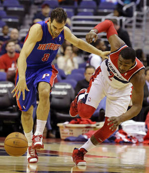 Photo - Detroit Pistons guard Jose Calderon, left, pushes away from Washington Wizards guard John Wall in the first half of an NBA basketball game on Wednesday, Feb. 27, 2013, in Washington. (AP Photo/Alex Brandon)