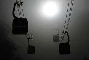 Photo - Gondolas are shrouded in fog as they travel to the Laura Cross-country Ski and biathlon venues during the 2014 Winter Olympics in Krasnaya Polyana, Russia, Sunday, Feb. 16, 2014.  (AP Photo/Dmitry Lovetsky)