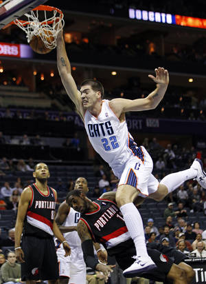 Photo - Charlotte Bobcats' Byron Mullens (22) dunks over Portland Trail Blazers' LaMarcus Aldridge (12) during the first half of an NBA basketball game in Charlotte, N.C., Monday, Dec. 3, 2012. (AP Photo/Chuck Burton)