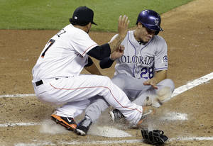 Photo - Colorado Rockies' Nolan Arenado (28) collides with Miami Marlins starting pitcher Henderson Alvarez, left, as he scores on a wild pitch in the fourth inning of a baseball game on Wednesday, April 2, 2014, in Miami.  (AP Photo/Lynne Sladky)
