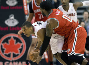 Photo - Toronto Raptors guard Kyle Lowry, left, battles for the ball against Milwaukee Bucks guard O.J. Mayo during first half NBA basketball game in Toronto, Monday, Jan. 13, 2014.  (AP Photo/The Canadian Press, Nathan Denette)