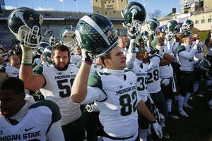 Photo - Michigan State tight end Josiah Price (82) celebrates with teammates after their 30-6 victory against Northwestern in an NCAA football game on Saturday, Nov. 23, 2013, in Evanston, Ill. (AP Photo/Andrew A. Nelles)