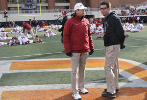 Photo - Oklahoma coach Bob Stoops and Oklahoma State coach Mike Gundy talk during the Bedlam college football game between the Oklahoma State University Cowboys (OSU) and the University of Oklahoma Sooners (OU) at Boone Pickens Stadium in Stillwater, Okla., Saturday, Dec. 7, 2013. Photo by Chris Landsberger, The Oklahoman