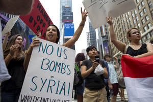 Photo - Rachel Lee Richards of New York. left, stands with opponents of a United States military strike against Syria as she and others protest at Times Square in New York Saturday, Aug. 31, 2013. (AP Photo/Craig Ruttle)