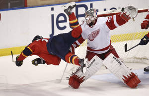 Photo - After hitting Detroit Red Wings goalie Jimmy Howard's (35) stick, Florida Panthers' Jesse Winchester falls to the ice during the third period of a NHL hockey game in Sunrise, Fla., Tuesday, Dec. 10, 2013. The Panthers won 3-2 in a shootout during overtime. (AP Photo/J Pat Carter)