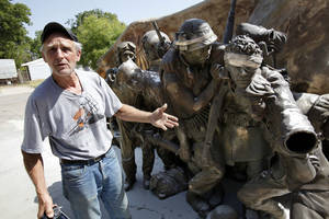 Photo - Sculptor Gareth Andrews stands next to his veterans' memorial monument Tuesday in Norman.  Photo by Steve Sisney, The Oklahoman