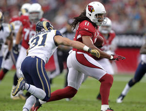 Photo - Arizona Cardinals wide receiver Larry Fitzgerald (11) gains yards as St. Louis Rams cornerback Cortland Finnegan (31) defends during the first half of an NFL football game, Sunday, Nov. 25, 2012, in Glendale, Ariz.  (AP Photo/Paul Connors)