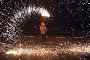 Photo - An Iranian man plays with a firework in the Pardisan Park in Tehran, Iran, Tuesday, March 18, 2014, during Chaharshanbe Souri, or Wednesday Feast, an ancient Festival of Fire, on the eve of the last Wednesday of the year, when Iranians jump over burning bonfires and throw firecrackers celebrating arrival of the spring which coincides with their new year, or Nowruz, which begins on March 21. (AP Photo/Vahid Salemi)