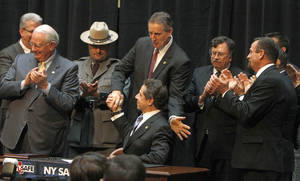 photo - NY Gov. Andrew Cuomo, seated at center, gets a congratulatory hand shake from Lt. Gov. Robert Duffy after signing the NY Safe Act during a signing ceremony at City Hall in Rochester Wednesday, Jan. 16, 2013.  Cuomo signed into law on Tuesday  legislation  that tightens a ban on assault-style rifles, calls for background checks on ammunition purchases, outlaws large-capacity magazines and tries to keep guns out of the hands of mentally ill people deemed to be a threat.  (AP Photo/Democrat & Chronicle, Shawn Dowd)  MAGS OUT; NO SALES