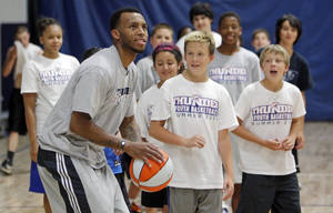 photo - OKLAHOMA CITY THUNDER NBA BASKETBALL PLAYER: Thunder guard Daequan Cook shows campers his shot during Thunder Youth Basketball Summer Camp at Santa Fe Family Life Center, 6300 N Santa Fe Ave., in Oklahoma City, Thursday, June 16, 2011.  Photo by Nate Billings, The Oklahoman ORG XMIT: KOD