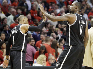 Photo - Brooklyn Nets forward Andray Blatche, right, celebrates with C.J. Watson during the second half in Game 6 of their first-round NBA basketball playoff series against the Chicago Bulls in Chicago, Thursday, May 2, 2013. The Nets won 95-92. (AP Photo/Nam Y. Huh)