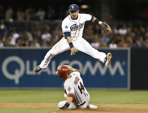 Photo - San Diego Padres shortstop Everth Cabrera sails over Arizona Diamondbacks' Paul Goldschmidt while relaying to first to complete a double during the eighth inning of a baseball game Friday, May 2, 2014, in San Diego.  (AP Photo/Lenny Ignelzi)