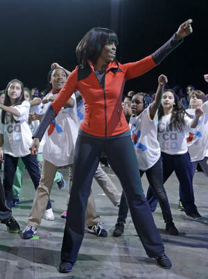 Photo - First lady Michelle Obama exercises with children from Chicago Public Schools, in her hometown of Chicago, Thursday, Feb. 28, 2013, as she makes a major announcement helping to bring back physical activity to area schools, while celebrating the third anniversary of her 'Lets Move' program.  (AP Photo/M. Spencer Green)