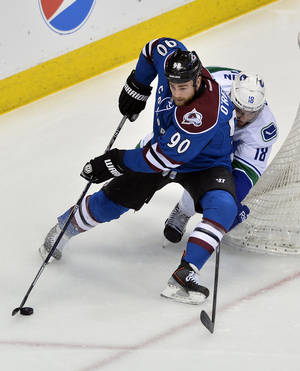 Photo - Colorado Avalanche center Ryan O'Reilly (90) moves the puck around Vancouver Canucks defenseman Ryan Stanton (18) during the first period of an NHL hockey game on Thursday, March 27, 2014, in Denver. (AP Photo/Jack Dempsey)