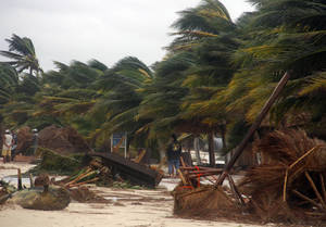 Photo -   People survey the damage caused by Hurricane Ernesto after it made landfall overnight in Mahahual, near Chetumal, Mexico, Wednesday, Aug. 8, 2012. (AP Photo/Israel Leal)