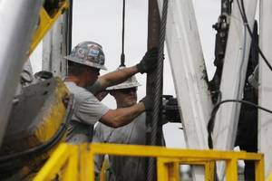 Photo -  Crew members with Anadarko Petroleum Corp. work on a drilling platform in 2009 on a Weld County farm near Mead, Colo. AP File Photo  <strong></strong>