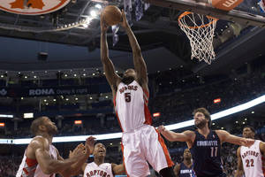 Photo - Toronto Raptors' Amir Johnson (5) claims a defensive rebound in front of Charlotte Bobcats Josh McRoberts, second from right, during second-half NBA basketball game action in Toronto, Friday, March 15 , 2013. (AP Photo/Canadian Press, Chris Young) ORG XMIT: CHY117