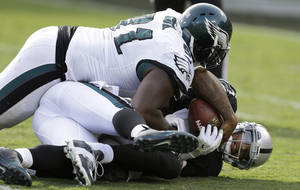 Photo - Oakland Raiders quarterback Terrelle Pryor, bottom, is sacked by Philadelphia Eagles defensive end Vinny Curry, obscured, as Philadelphia Eagles defensive end Fletcher Cox (91) lays on top during the third quarter of an NFL football game in Oakland, Calif., Sunday, Nov. 3, 2013. (AP Photo/Ben Margot)
