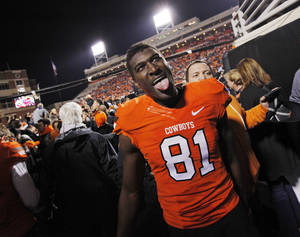 Photo - OSU's Justin Blackmon (81) reacts as he leaves the field after the Bedlam college football game between the Oklahoma State University Cowboys and the University of Oklahoma Sooners at Boone Pickens Stadium in Stillwater, Okla., Saturday, Dec. 3, 2011. OSU beat OU, 44-10. Photo by Nate Billings, The Oklahoman