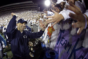 Photo - In this image made with a fisheye lens, Penn State head coach Bill O' Brien celebrates with students after a 43-40 win over Michigan during an NCAA college football game in State College, Pa., Saturday, Oct. 12, 2013.  (AP Photo/Gene J. Puskar)