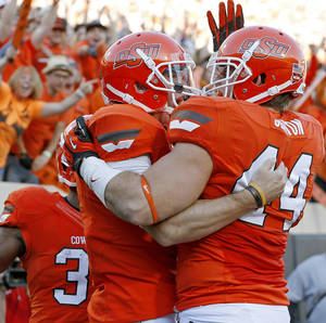 photo - Oklahoma State's J.W. Walsh (4) celebrates with Jeremy Seaton (44) after a touchdown during a college football game between Oklahoma State University (OSU) and Texas Tech University (TTU) at Boone Pickens Stadium in Stillwater, Okla., Saturday, Nov. 17, 2012.  Photo by Bryan Terry, The Oklahoman