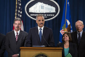 Photo - Attorney General Eric Holder, center, speaks during a news conference at the Justice Department, on Monday, May 19, 2014, in Washington. The Justice Department on Monday charged Credit Suisse AG with helping wealthy Americans avoid paying taxes through offshore accounts, and a person familiar with the matter said the European bank has agreed to pay about $2.6 billion in penalties. From left, Deputy Attorney General James Cole, Holder, Assistant Attorney General for the Tax Division Kathryn Keneally, and IRS Commissioner John Koskinen (AP Photo/ Evan Vucci)