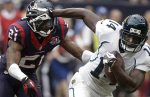 Photo -   Jacksonville Jaguars wide receiver Justin Blackmon (14) breaks away from Houston Texans' Brice McCain (21) to score a touchdown during the fourth quarter of an NFL football game on Sunday, Nov. 18, 2012, in Houston. (AP Photo/Patric Schneider)