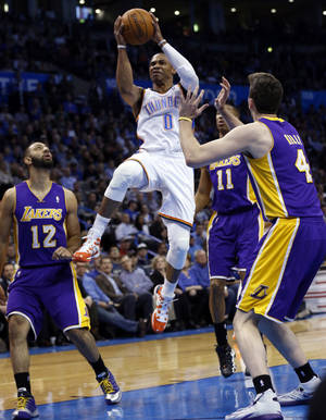 Photo - Thunder guard Russell Westbrook scores during Thursday night's matchup against the Lakers.