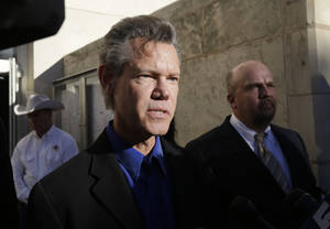 photo - Entertainer Randy Travis, center, makes comments after exiting the Grayson County Courthouse with an unidentified person, right, Thursday, Jan. 31, 2013, in Sherman, Texas. Travis plead guilty to driving while intoxicated in a plea agreement with the court and will pay a $2,000 fine and serve a two year probation. (AP Photo/Tony Gutierrez)