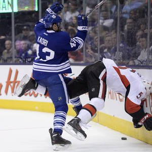 Photo - Toronto Maple Leafs' Nazem Kadri hits Ottawa Senators' Cody Ceci head first into the boards during second period of an NHL hockey game in Toronto, Saturday, Feb. 1, 2014. (AP Photo/The Canadian Press, Frank Gunn)