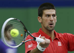 Photo -   Novak Djokovic of Serbia returns a shot to Grigor Dimitrov of Bulgaria during their second round men's singles match of the Shanghai Masters tennis tournament at Qizhong Forest Sports City Tennis Center in Shanghai, China, Wednesday Oct. 10, 2012. Djokovic won 6-3, 6-2. (AP Photo/Kin Cheung)
