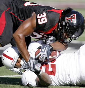 Photo - Texas Tech's Maron Williams brings down OU's Chris Brown during the college football game between the University of Oklahoma Sooners (OU) and Texas Tech University Red Raiders (TTU ) at Jones AT&T Stadium in Lubbock, Texas, Saturday, Nov. 21, 2009. Photo by Bryan Terry, The Oklahoman